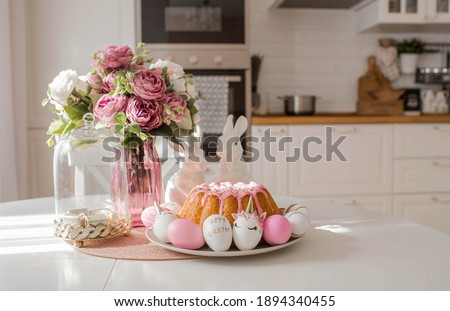 Banner. Minimal concept. Easter cake, rabbits and eggs in the form of a unicorn and with a gold pattern on a white table. Copy space for text.