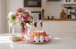 Banner. Minimal easter concept. Easter cake, rabbits and eggs in the form of a unicorn and with a gold pattern on a white table. Copy space for text. The portfolio contains more Easter pictures.