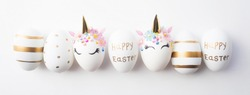 Banner. Minimal easter concept. Easter eggs in the form of a unicorn, and with a gold pattern on a white background. Flat lay. Copy space for text. The portfolio has more Easter pictures.