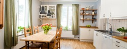 banner of acozy kitchen with tulips on the table and green curtains by the two windows