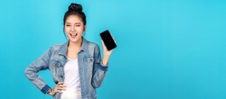 Banner of asian woman feeling happiness, blinks eyes and standing hold smartphone on blue background. Cute asia girl smiling wearing casual jeans shirt and connect internet shopping online and present
