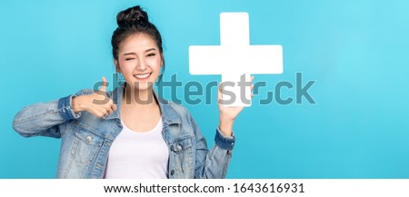 Photo of  Banner of asian woman smiling, showing plus or add sign and thumb up on blue background. Cute asia girl wearing casual jeans shirt and showing join sign for increse and more benefit concept