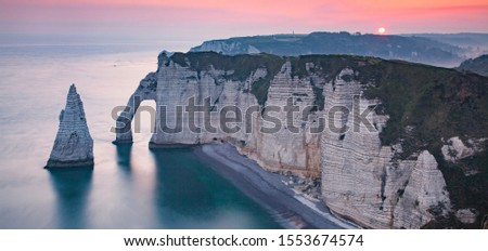 banner of coastal landscape along the Falaise d'Aval the famous white cliffs of Etretat village with the Porte d'Aval natural arch and the rock known as the Aiguille d'Etretat #1553674574