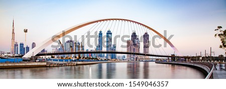 banner of colorful sunset over Dubai Downtown skyscrapers and the newly built Tolerance bridge as viewed from the Dubai water canal