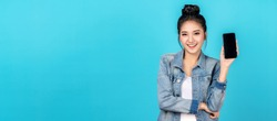 Banner of Happy asian woman feeling happiness and standing hold smartphone on blue background. Cute asia girl smiling wearing casual jeans shirt and connect internet shopping online and present