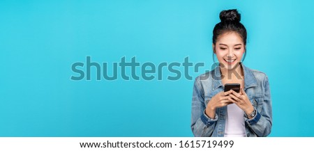Banner of Happy asian woman feeling happiness and standing typing smartphone on blue background. Cute asia girl smiling wearing casual jeans shirt and connect internet shopping online and surfing.