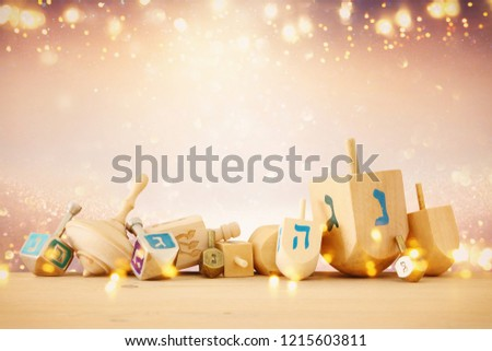 Banner of jewish holiday Hanukkah with wooden dreidels (spinning top) over glitter shiny background