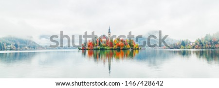 Banner of lake Bled in Slovenia. Charming autumn panorama landscape of island with church rounded colorful trees in the middle of Bled lake. Colorful autumn scenery, popular travel destination.