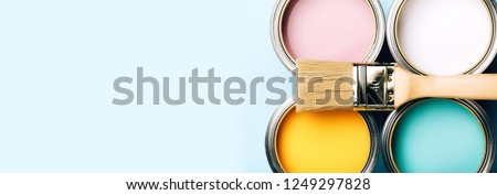 Banner of renovation concept. Brush with wooden handle on opened cans on blue pastel background. Yellow, white, pink, turquoise colors. Macro. ストックフォト ©