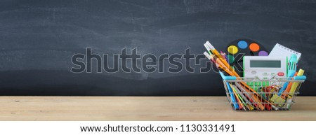 Banner of Shopping cart with school supply in front of blackboard. Back to school concept