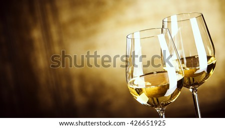 Banner of Two glasses of white wine standing side by side in a close up view over a panoramic abstract brown background with copy space #426651925