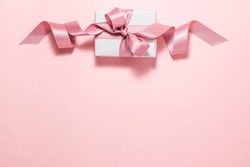 Banner of white paper gift box with a purple satin ribbon bow on pink background at the top. Flat lay top view with copyspace. Gift and holidays concept from above