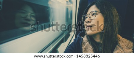 Banner or web page of Asian Young lady passenger Sitting in depressed mood beside the window inside Train which travel between town when travel alone for escape the chaos,traveller and depress concept