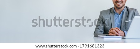 Banner panorama of faceless mid body section young smiling cheerful businessman entrepreneur in bright white modern office facing towards camera copy space for text Stock fotó ©