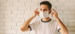 Banner panorama of young confident man wearing medical mask on face for protection against coronavirus nCov-19. Professional doctor putting on protective face mask. COVID-19 preventive measures