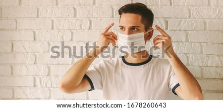 Banner panorama of young confident man wearing medical mask on face for protection against coronavirus nCov-19. Professional doctor putting on protective face mask. COVID-19 preventive measures Foto d'archivio ©