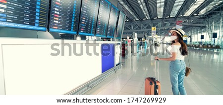 Photo of  Banner photo of Asian female wearing face mask with suitcase checking flight cancellation status on airport information board in empty airport. airline bankrupt, airline crisis or new normal concept