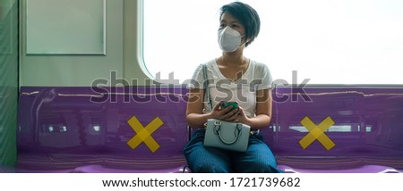 Banner photo of Asian female woman sitting in subway distance for one seat from other people a social distancing for protect coronavirus a new normal trend. Social distancing or new normal concepts