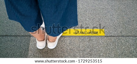 Banner photo of Asian woman standing on social distancing sign for keep distance and queue for entrance subway train a new normal life trend. corona virus, social distancing or new normal concepts