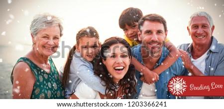 Banner sending love against happy family posing at beach #1203366241