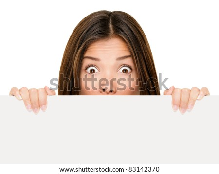 Banner sign woman peeking over edge of blank empty paper billboard with copy space for text. Beautiful Asian Caucasian woman looking surprised and scared - funny. Isolated on white background. - stock photo