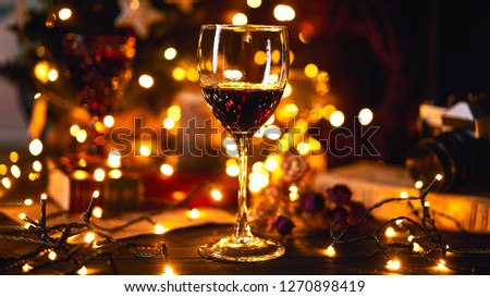 Banner size 16 in 9. Festive atmosphere in the evening with a glass of red wine. Light bokeh on background. Christmas, New Year's or Saint Valentine holiday. Golden color and soft focus.