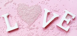 Banner.The word love in white letters on a trendy pink background. Happy Valentine's Day, Mother's Day, March 8, World Women's Day holiday card concept. Flat lay.