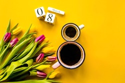 Banner.Two cups of hot, morning coffee in the shape of the number 8 and a bouquet of yellow-lilac tulips on a bright yellow background. View from above.Copy space for text. The concept of holidays.