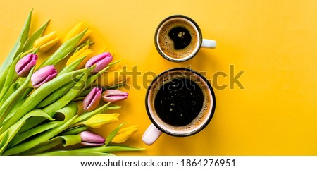 Banner.Two cups of hot, morning coffee in the shape of the number 8 and a bouquet of yellow-lilac tulips on a bright yellow background. View from above.Copy space for text. The concept of holidays. Foto stock ©