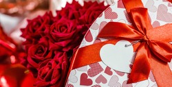 Banner. Valentine's day. Red roses in a white box in the form of a heart on the background of foil balls. A gift for women on a holiday. The concept of delivering flowers. floristry and flower shops.