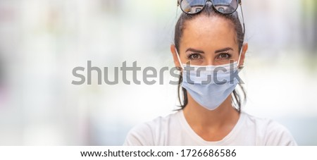 Banner view of face of a pretty girl with sunglasses on her forehead, wearing a disposable face mask.
