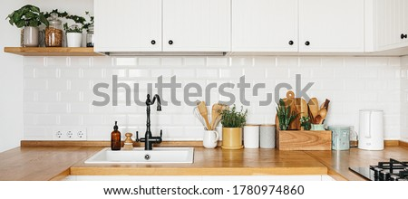 Banner View on white kitchen in scandinavian modern style, kitchen details, plants on wooden table, white ceramic brick wall background. Sustainable living eco friendly kitchen.