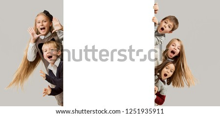 Banner with a surprised children peeking at the edge with copyspace. The portrait of cute little kids boy and girls looking at camera against white studio wall. Kids fashion. Sublings day.