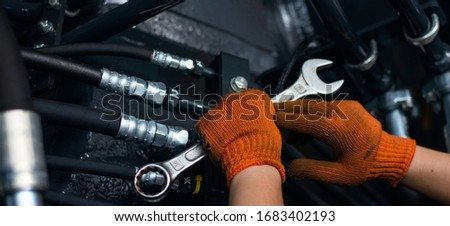 Banner with close up view of hydraulic pipes of heavy industry machine and hands of mechanic. Low key. Hydraulic maintenance concept. Photo stock ©