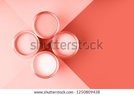 Banner with color of the year 2019 - Living Coral. Four open cans of paint on bright symmetry background. Place for text. Renovation concept.