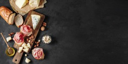 Banner with delicious snack of prosciutto, cheese, nuts and honey. Wooden chopping board. Dark textured background. Appetizer, aperitif, snack table. Top view. Space for text.