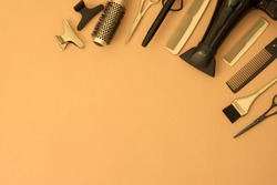 Banner with hairdressing tools. Gold and black hair salon accessories in the corner on an orange and yellow background with space for text. Hair dryer, comb, scissors, brush and hair clips.