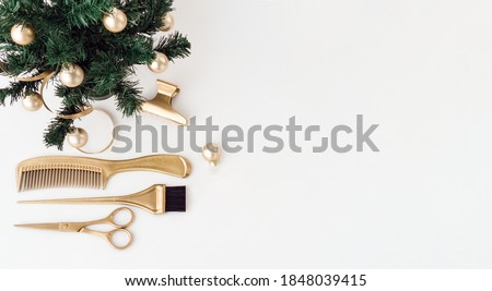 Banner with hairdressing tools in gold color and a Christmas tree on a white background. Holiday template with hair salon accessories with space for text. Flat lay with Hairstylist's scissors.