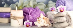 Banner with massage stones, seashell, burning candles, rolled towels, soap, massage oil, sea salt, flowers, abstract lights. Spa resort therapy composition Soft focus