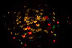 Banner with multicolored defocused lights garlands in form of heart. Bokeh on a black background for use in the photo editor. Beautiful bright curly bokeh. Magic background for new year and Christmas.