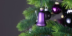 Banner with purple bells haped glass tree bauble on decorated Christmas tree with other seasonal tree ornaments on dark black background