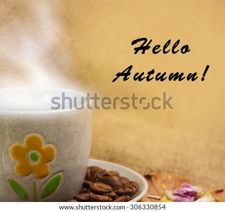 Banner with words hello autumn and the cup of coffee lying on the books with dry yellow maple leaves and everlasting flowers on sackcloth background