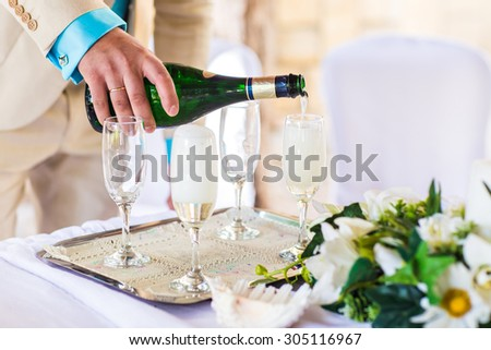 Banquet event. Man pouring champagne into glass. #305116967