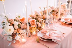 Banquet, restaurant. Table setting. Pink plates, gold cutlery, glasses. On the table is a pink tablecloth. Peach-colored napkin with a golden ring. Floral arrangements in peach pink hues. Tall candles