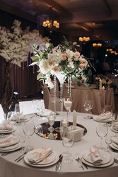 Banquet table covered with white tablecloths with white plates, silver cutlery, white napkins with pink ribbon. Bouquet of roses and wine glasses on the festive table with white tablecloth.