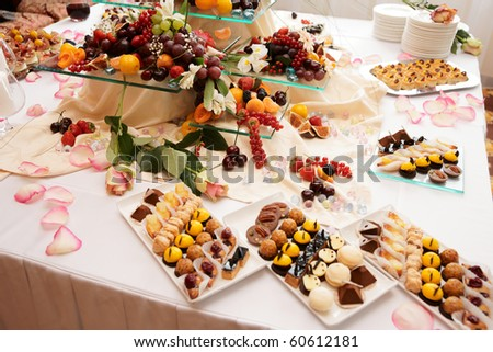 Banquet table full of fruits and berries - catering event, wide angle shot - stock photo