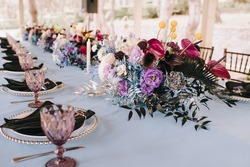 Banquet table in nature. Rack and cutlery, purple glasses, black napkins. Flower arrangement of violet, blue, black, silver flowers, anthurium, roses, carnations, eustomas. Blue tablecloth.
