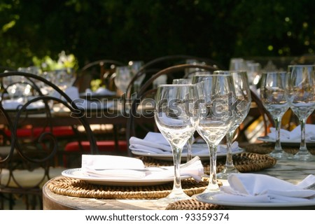 Banquet table in South africa with glasses and napkins under a big tree