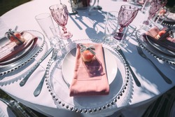 Banquet table on a green lawn. Racks and cutlery, velvet napkins, pink glasses. Floral arrangement of pink flowers. Silver candlesticks and candles. On the table is a white tablecloth.