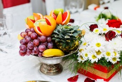 Banquet table served with delicious food. Fresh grapes, orange, kiwi, grapefruit, banana decorated with flowers. Fruit dessert